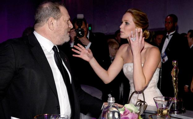 Jennifer Lawrence (d) habla con Harvey Weinstein en una fiesta.