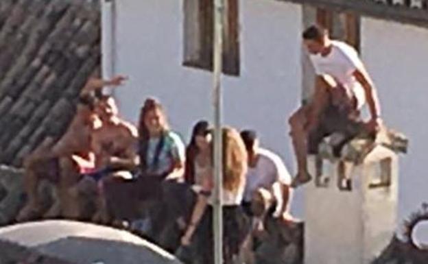 Un grupo de jóvenes subido al tejado de un edificio del Albaicín.